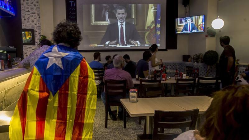 Varias personas miran en televisión en un bar en Barcelona el discurso del rey Felipe VI tras el referendum del 1-O. EFE/QUIQUE GARCÍA