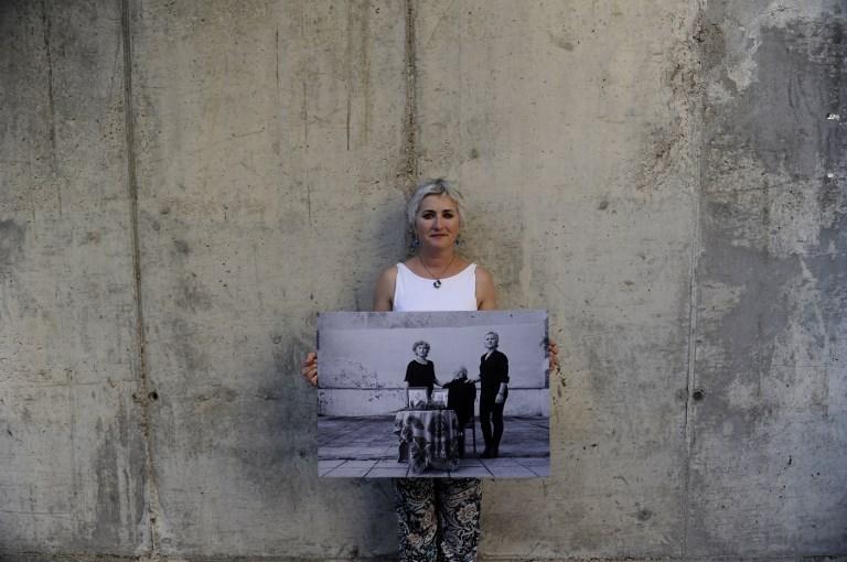 Paqui Maqueda posa sosteniendo una foto que muestra a su bisabuelo Juan Rodríguez Tirado (L) asesinado a tiros por un pelotón de fusilamiento de la época de Franco durante la guerra civil española. AFP