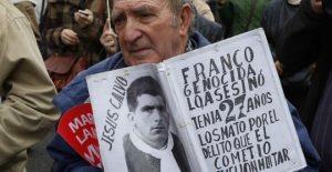 Un hombre muestra una foto de una víctima del franquismo. EFE/Paco Campos