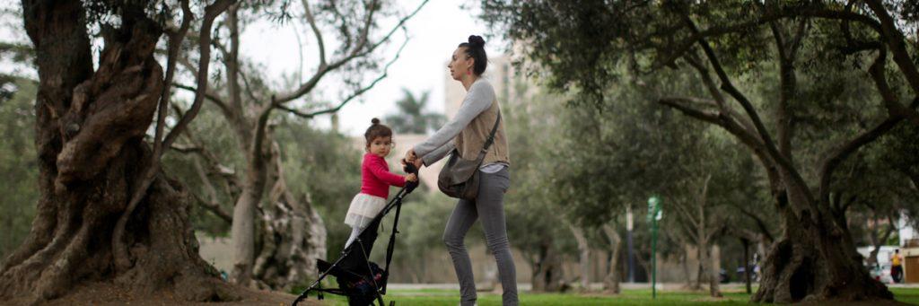 Una mujer pasea a una niña por un parque.- EFE