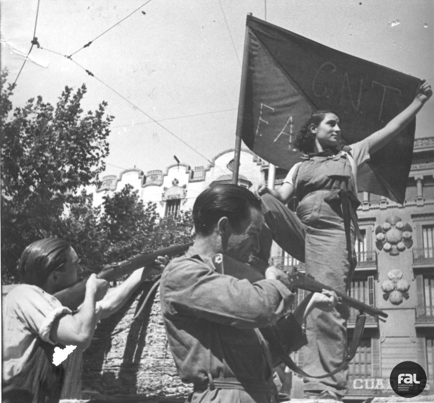 miliciana desplegando la bandera rojinegra de la libertad sobre una barricada en las Ramblas (Barcelona) tras la victoria sobre los fascistas.- Fundación Anselmo Lorenzo