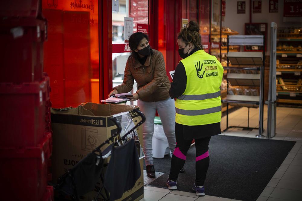 Carmen Nava (izquierda) durante su turno de recogida de alimentos donados en la puerta de una supermercado del barrio de Chamberí, en Madrid, el 4 de marzo de 2021. Jairo Vargas