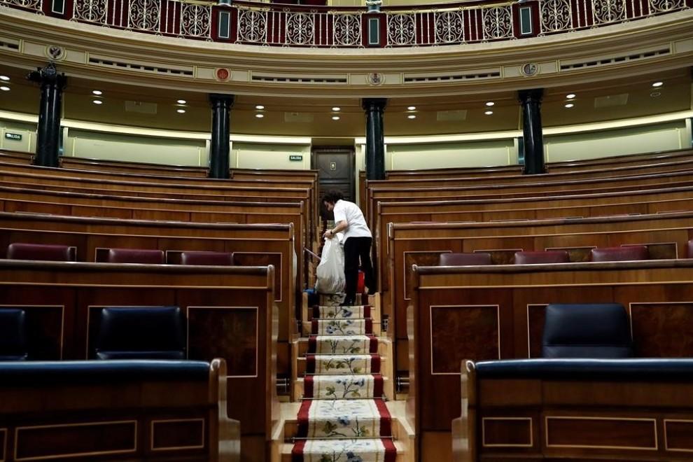 Una limpiadora en el hemiciclo del Congreso de los Diputados, vacío tras la entrada en vigor del estado de alarma. EFE