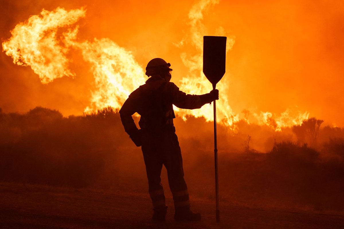 Bomberos trabajan en un incendio forestal entre Navalacruz y Riofrío (Ávila), en agosto de 2021.- CÉSAR MANSO / AFP