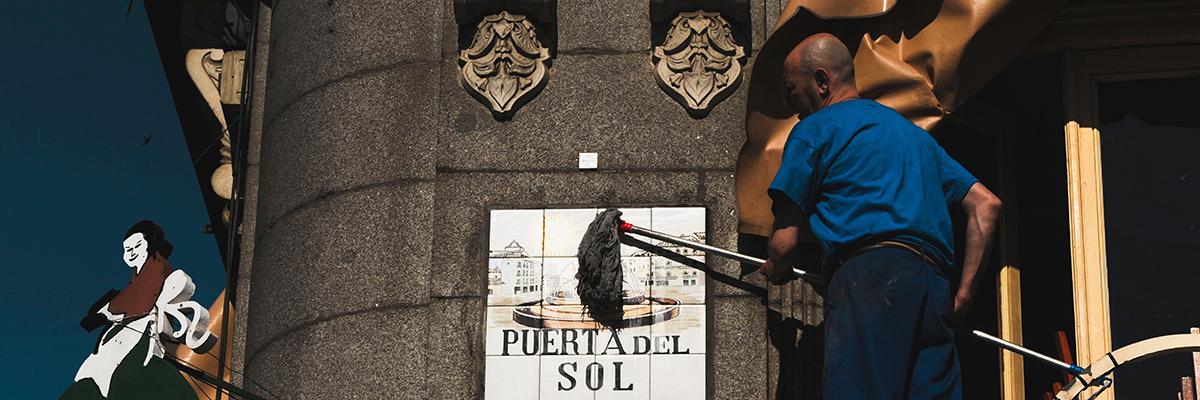 Un operario del Ayuntamiento de Madrid limpia el cartel de la Puerta del Sol- FERNANDO SANCHEZ