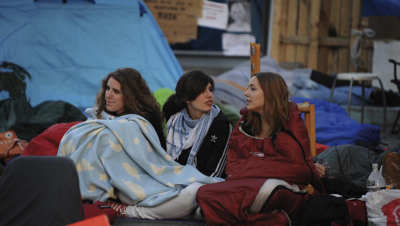 Fotografía: Tres jóvenes conversan tras haber dormido en la Puerta del Sol durante la acampada del movimiento 15-M.- FERNANDO SÁNCHEZ