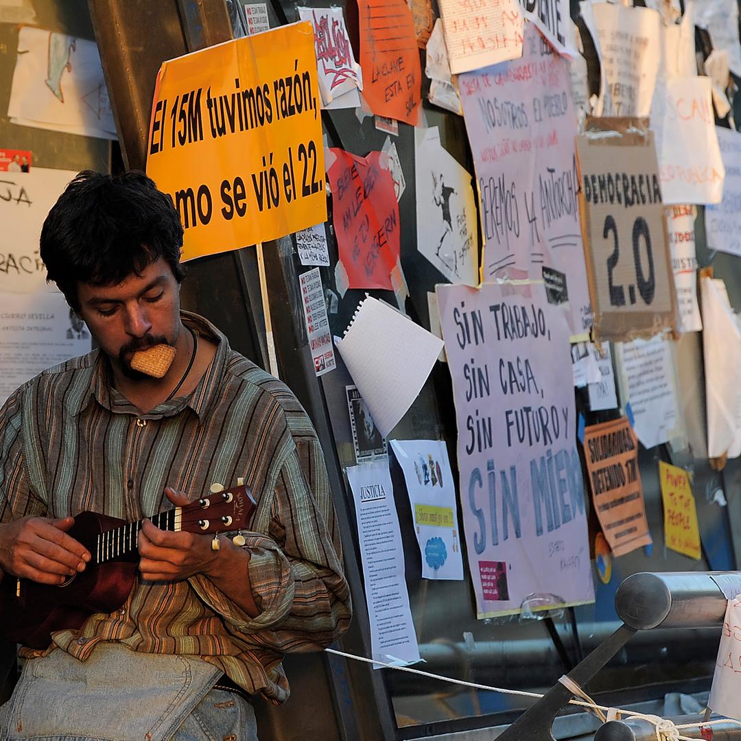 Fotografía: Un manifestante toca el ukelele en la Puerta del Sol en mayo de 2011.- DANI POZO / AFP