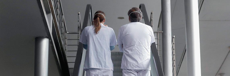 Dos sanitarias en unas escaleras mecánicas en un hospital madrileño.- EFE